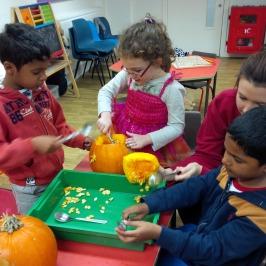 children carving pumpkins